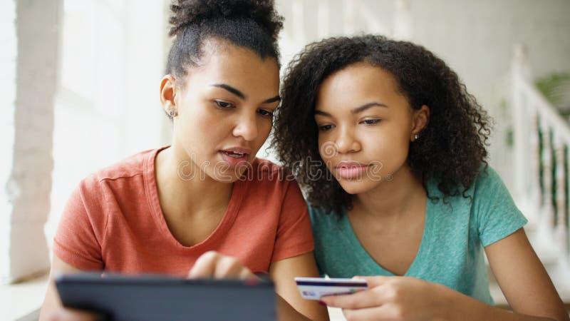 Due amiche ricce allegre della corsa mista che comperano online con il computer della compressa e la carta di credito a casa immagine stock libera da diritti