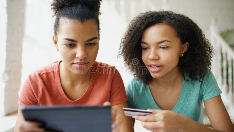 Due amiche ricce allegre della corsa mista che comperano online con il computer della compressa e la carta di credito a casa fotografia stock libera da diritti