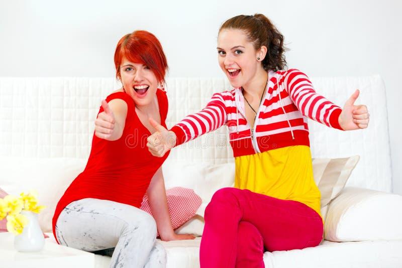 Due amiche sorridenti che mostrano i pollici aumentano il gesto fotografia stock libera da diritti