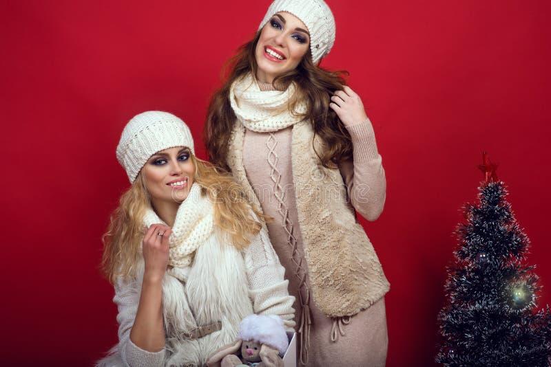 Due amiche splendide con i sorrisi perfetti che indossano woole bianco fotografia stock