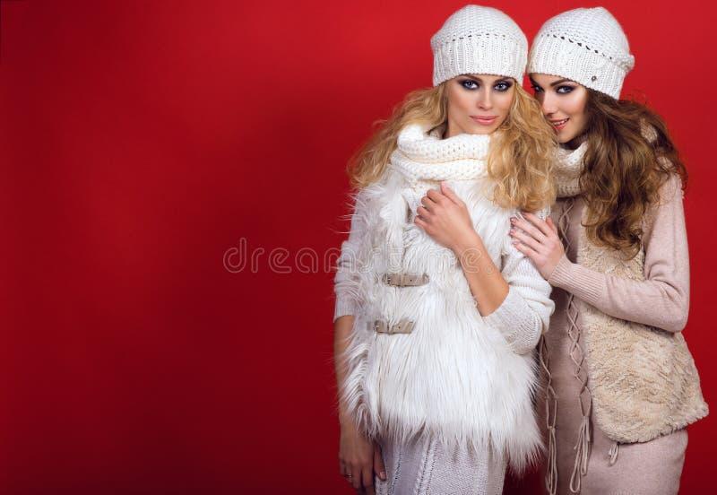 Due amiche splendide con i sorrisi perfetti che portano i cappelli, le sciarpe, i maglioni ed i panciotti di lana bianchi sui pre fotografie stock libere da diritti
