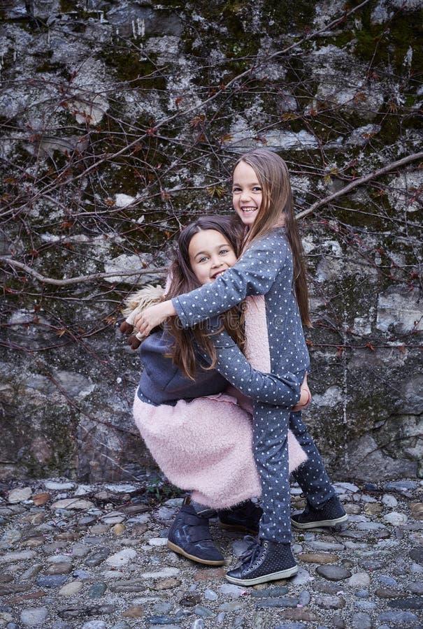 Due amiche sveglie che si abbracciano immagini stock libere da diritti