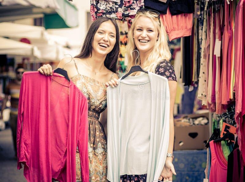 Due amici al centro commerciale che sceglie i vestiti immagini stock libere da diritti