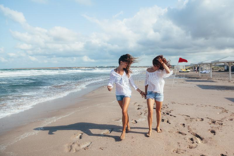 Due amici che camminano sulla spiaggia fotografie stock libere da diritti