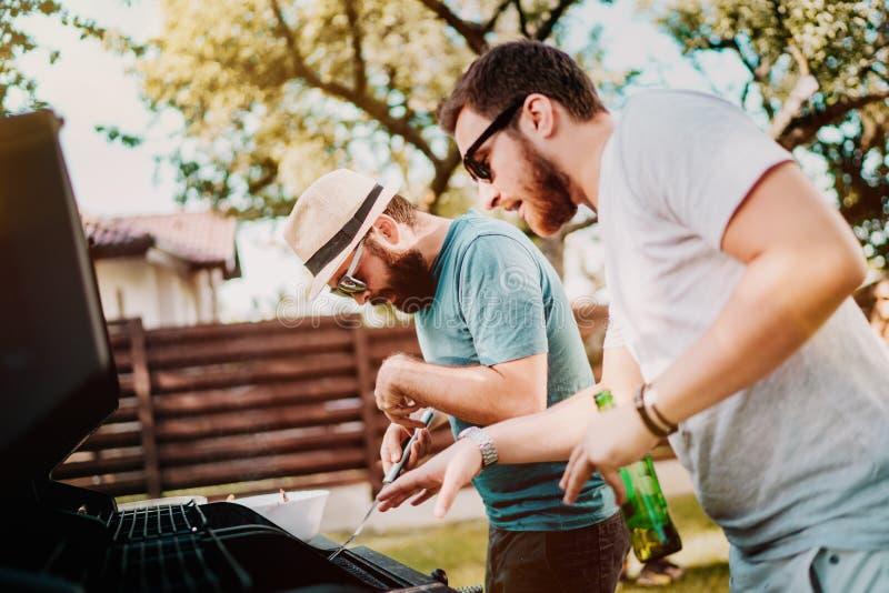 Due amici che cucinano e che si divertono su una griglia del barbecue durante il partito del cortile di domenica immagine stock