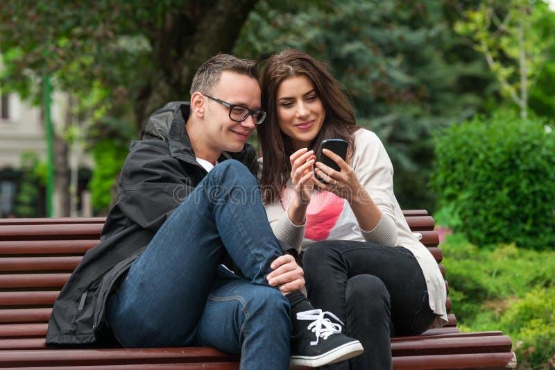 Due amici che dividono uno smartphone su un banco di parco fotografie stock