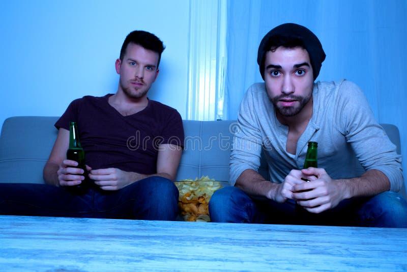 Due amici che guardano appassionato TV con birra e le patatine fritte fotografie stock