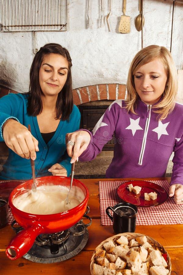 Due amici che mangiano fonduta immagine stock libera da diritti