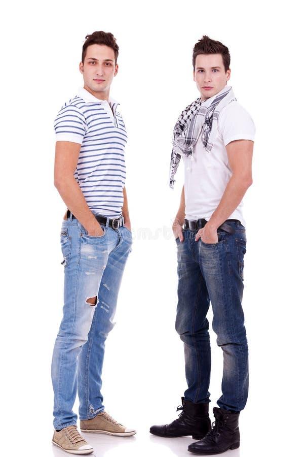 Due amici che si levano in piedi con le loro mani in caselle fotografie stock