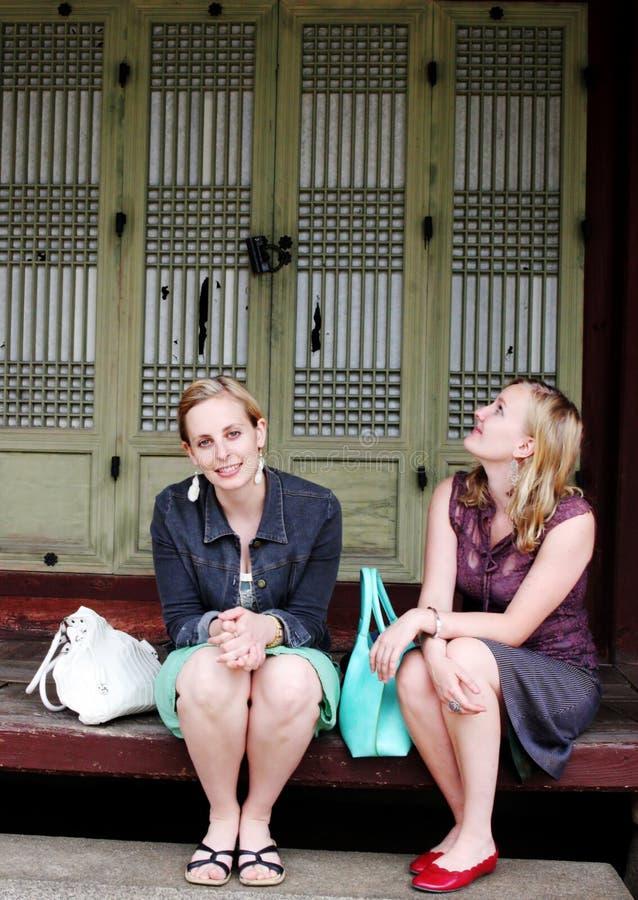 Due amici che si siedono su un punto fotografie stock