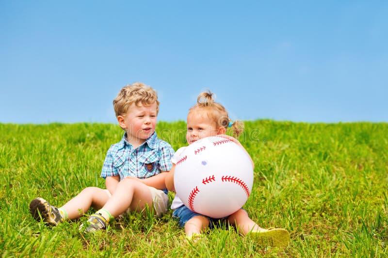 Due amici che si siedono sull'erba fotografia stock