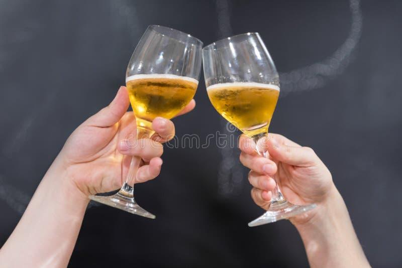 Due amici che tostano con i vetri di birra al pub Fondo della lavagna fotografia stock