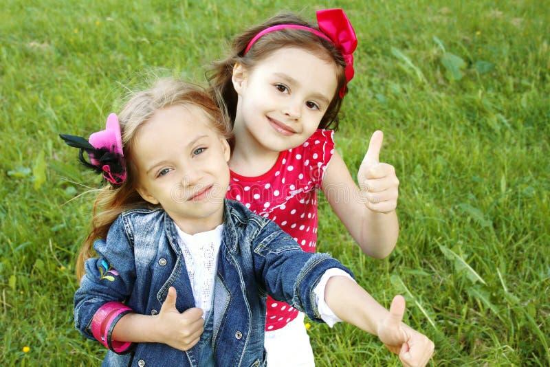 Due amici delle bambine. Pollici in su fotografie stock libere da diritti