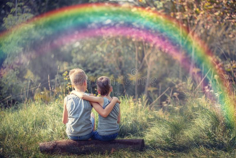 Due amici di ragazzini che tengono e che godono della natura con l'arcobaleno nel giorno di estate soleggiato immagini stock libere da diritti