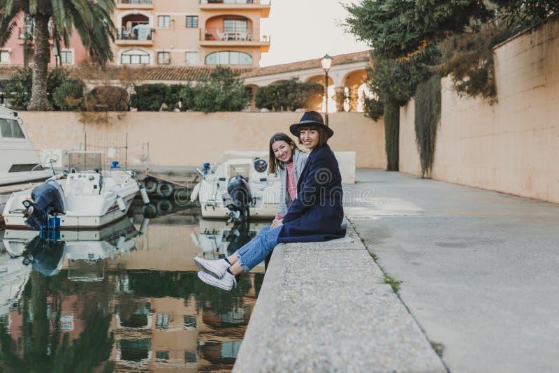 Due amici felici che si siedono sul bacino al porto, divertentesi e parlanti sulla via Aria aperta di stile di vita fotografia stock