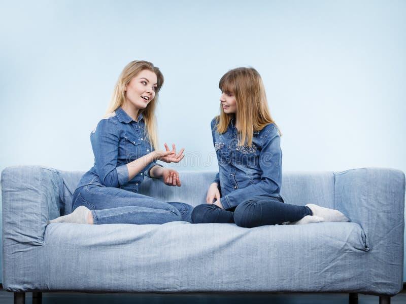 Due amici felici delle donne che indossano conversazione dell'attrezzatura dei jeans immagini stock