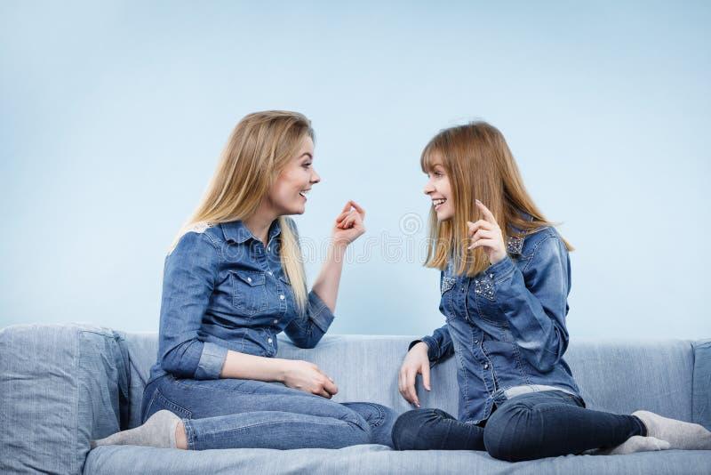 Due amici felici delle donne che indossano conversazione dell'attrezzatura dei jeans fotografia stock libera da diritti