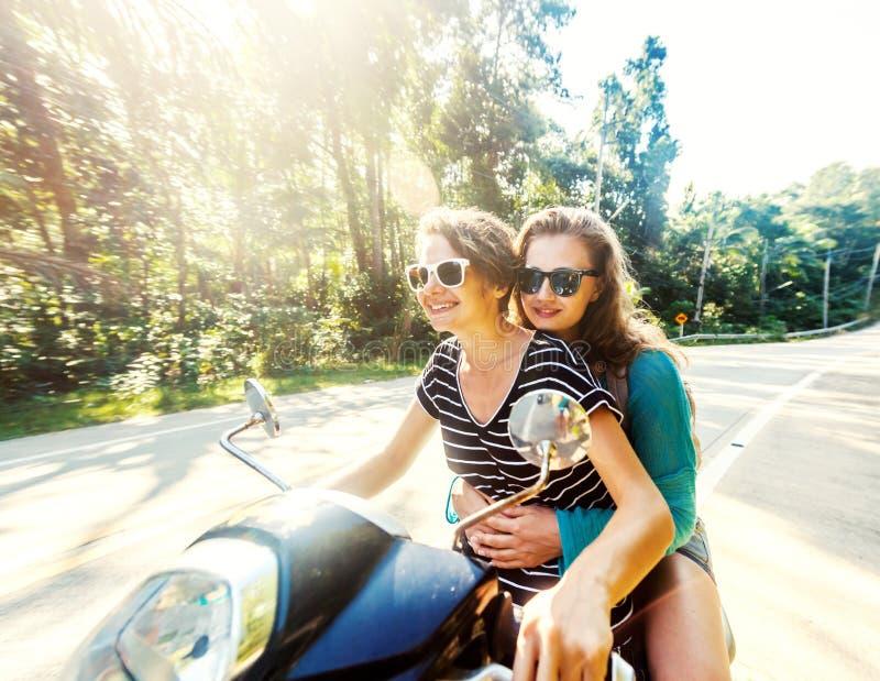 Due amici felici su una bici guidano attraverso la giungla tropicale fotografie stock
