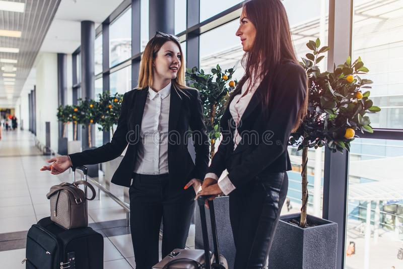 Due amici femminili allegri che aspettano un aereo che sta nel corridoio dell'aeroporto con bagagli pesanti vicino ai portoni fotografia stock