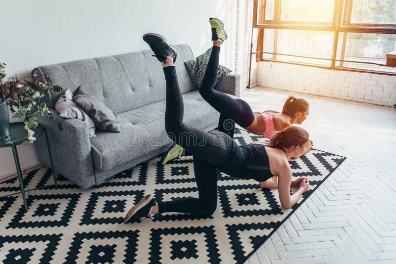 Due amici femminili allegri che fanno l'estremità che tonifica l'asino d'esecuzione di esercizio dà dei calci a a casa fotografie stock libere da diritti