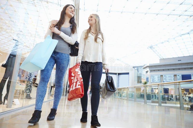Due amici femminili che comperano insieme nel centro commerciale fotografia stock