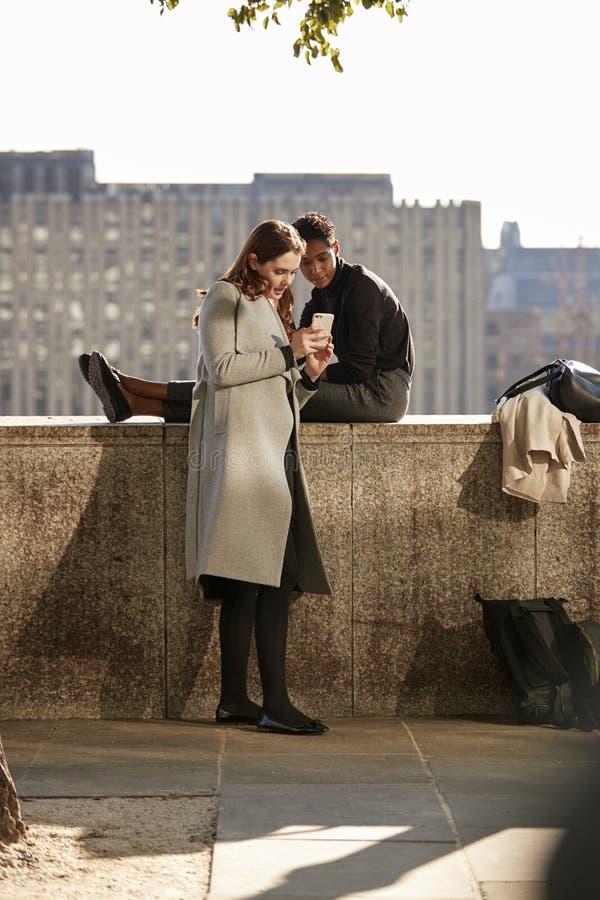 Due amici femminili che prendono una rottura sull'argine dal Tamigi, esaminante uno smartphone, retroilluminato fotografia stock libera da diritti