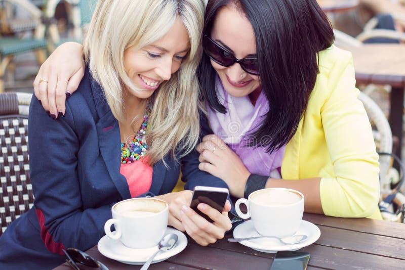 Due amici femminili che si siedono e che osservano le foto sul telefono cellulare immagine stock libera da diritti