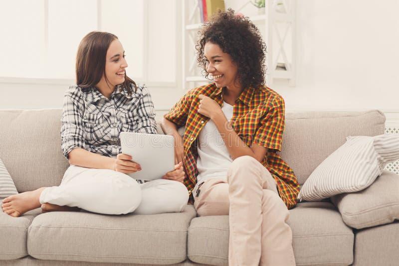 Due amici femminili felici che per mezzo della compressa fotografie stock libere da diritti