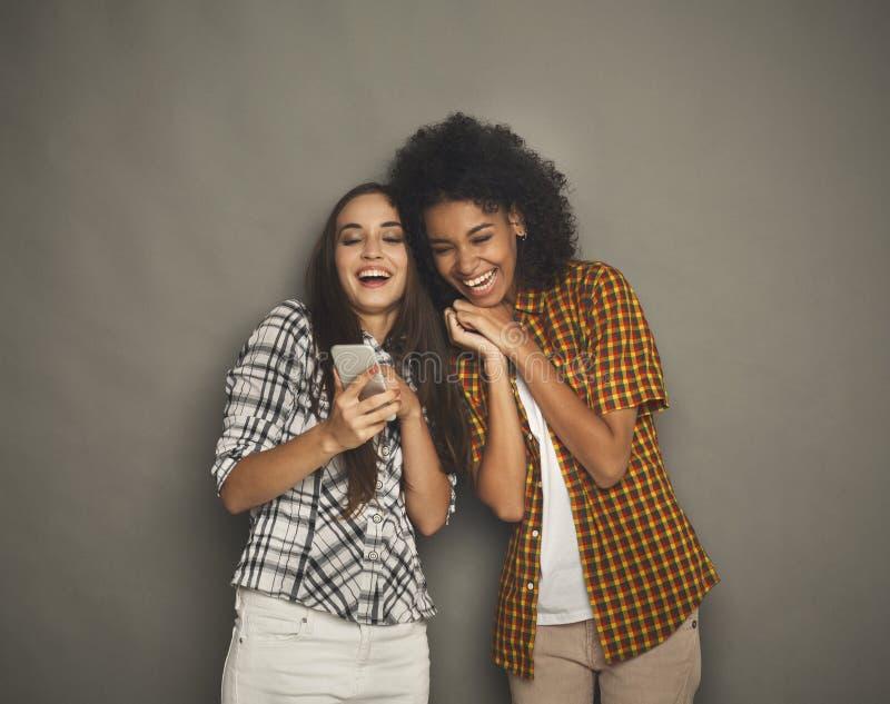 Due amici femminili felici che per mezzo dello smartphone fotografia stock libera da diritti