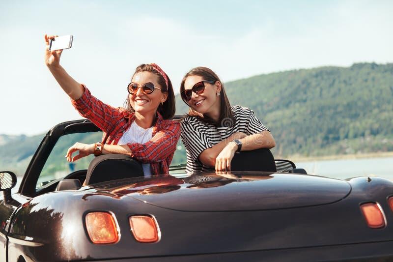 Due amici femminili prendono la foto del selfie in automobile del cabriolet con il beaut fotografie stock