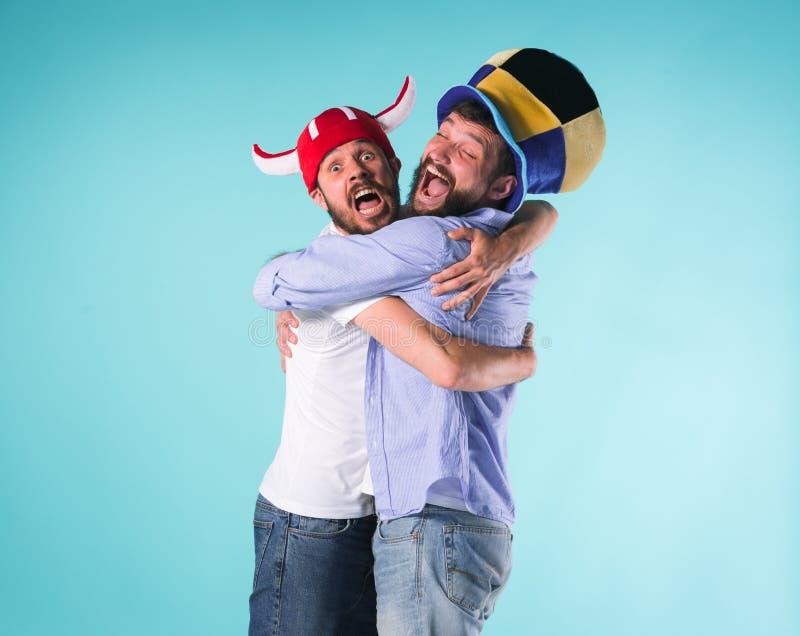 Due amici maschii eccitati celebrano gli sport di sorveglianza fotografie stock