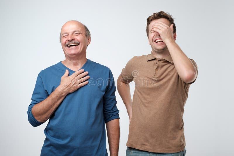 Due amici nell'usura variopinta casuale che sta insieme e che ride Migliori amici che godono della vita Due uomini che hanno dive fotografia stock libera da diritti