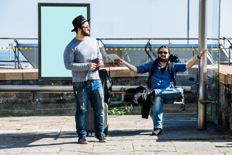 Due amici sono aspettanti e infuriantesi a causa del ritardo fotografia stock libera da diritti