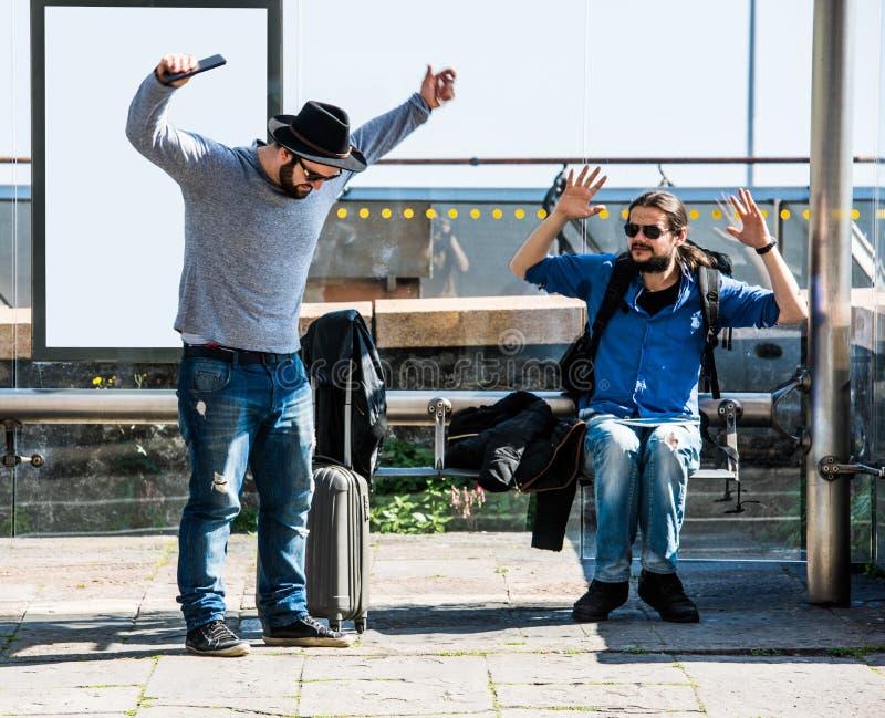Due amici stanno infuriando a causa del ritardo del bus fotografia stock