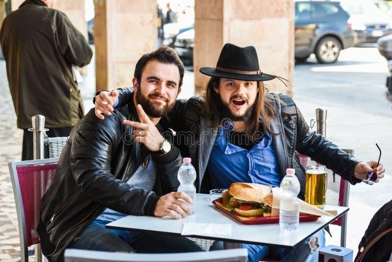 Due amici/turisti affamati stanno mangiando fuori all'aperto immagini stock