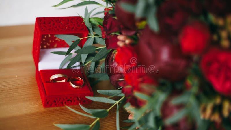 Due anelli alla scatola vicino ai fiori fotografia stock