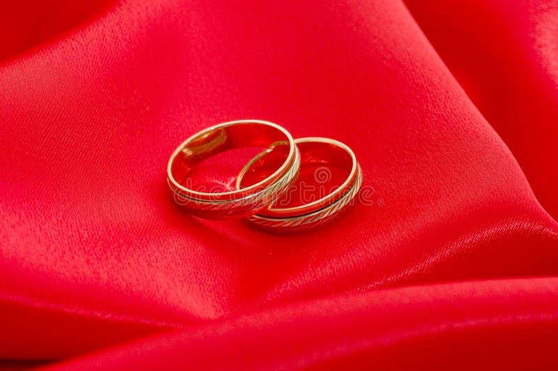 Due anelli di cerimonia nuziale dell'oro sul colore rosso fotografia stock libera da diritti