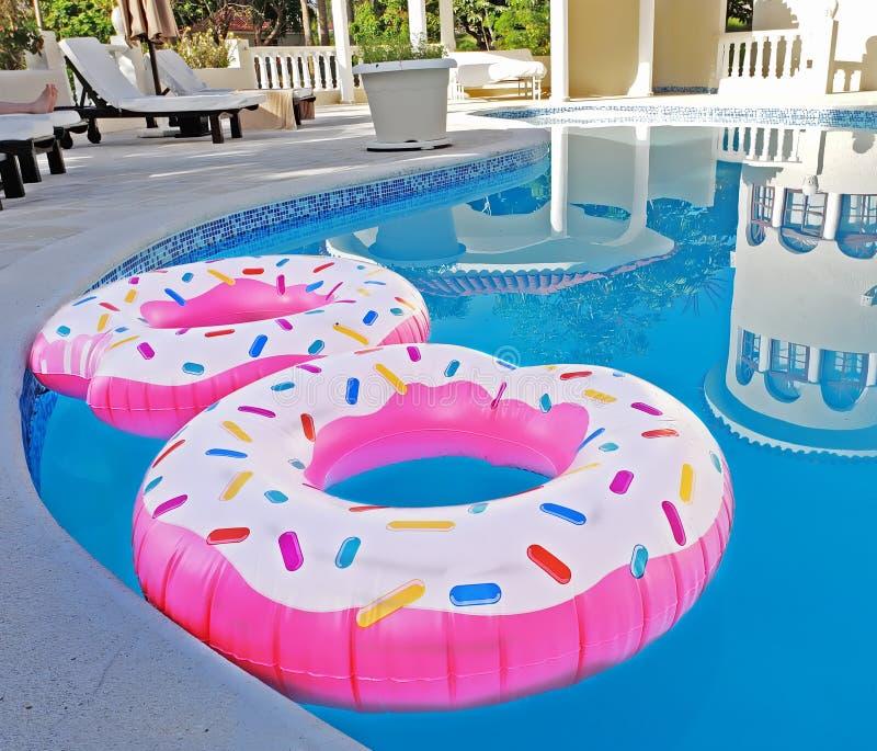 Due anelli rosa del galleggiante in una piscina fotografia stock libera da diritti