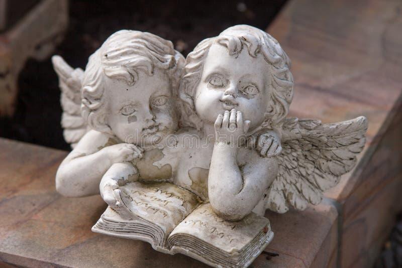 Due angeli che leggono un libro fotografia stock