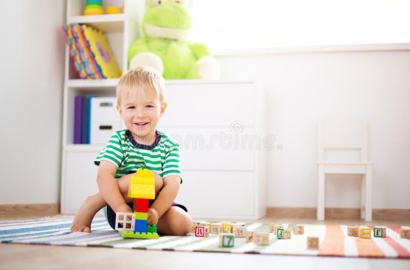 Due anni del bambino che si siede sul pavimento con i cubi di legno fotografia stock libera da diritti