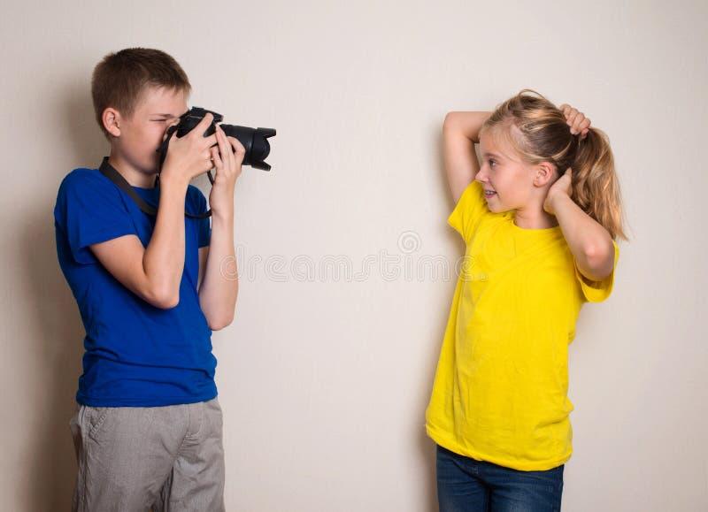 Due anni dell'adolescenza dei migliori amici che fanno foto sulla loro macchina fotografica a casa, divertendosi insieme, sulla g immagini stock libere da diritti