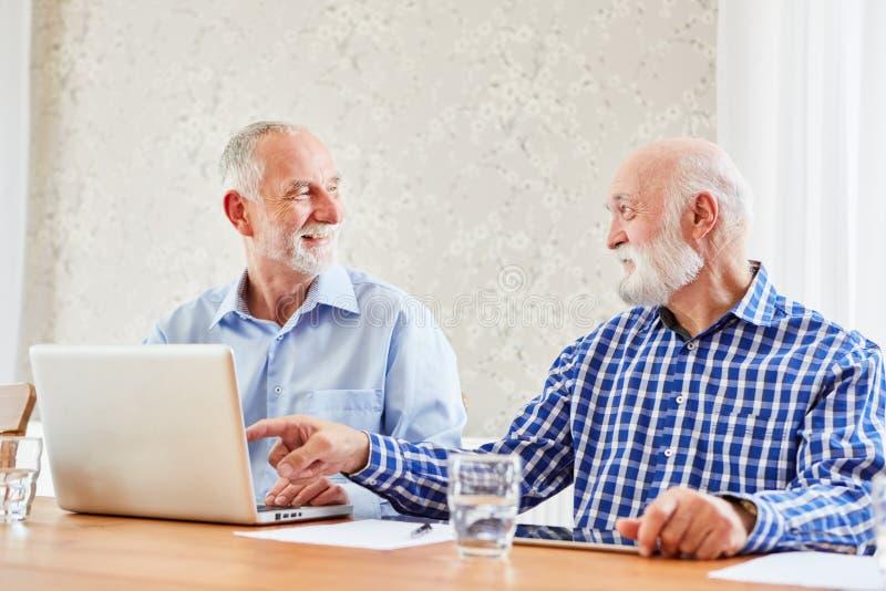 Due anziani al computer portatile stanno divertendo immagini stock