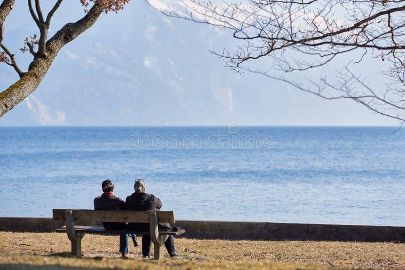 Due anziani si siedono su un banco ed esaminano il lago Traunsee Il lago è situato vicino alla città di Gmunden fotografia stock libera da diritti