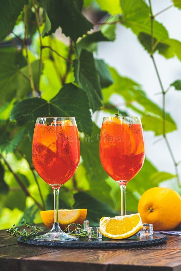 Due Aperol spritz il cocktail in grande vetro di vino con le arance, bevanda fredda dell'alcool fresco italiano dell'estate Giard fotografia stock