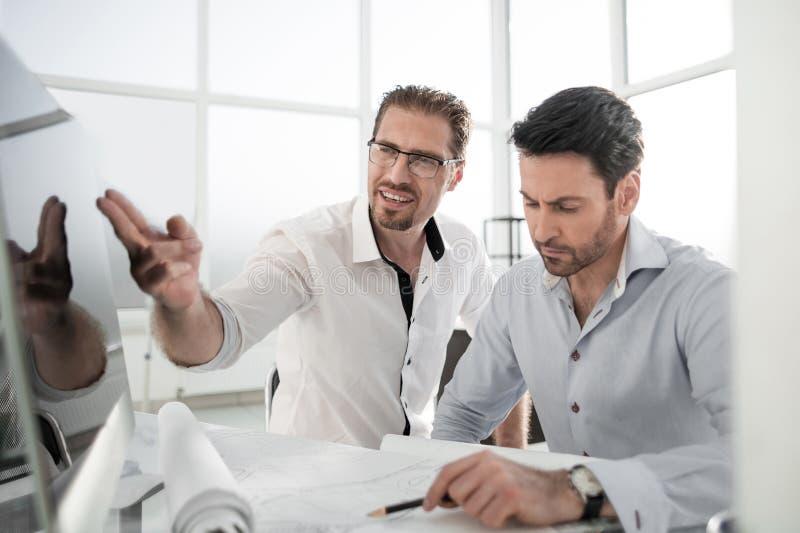 Due architetti che discutono il progetto nell'ufficio fotografia stock libera da diritti