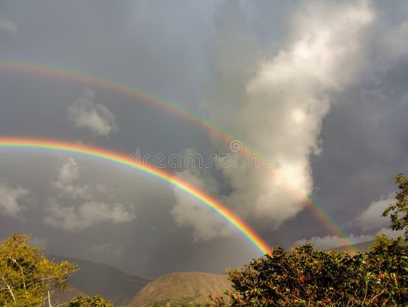 Due arcobaleni su un cielo tempestoso fotografia stock libera da diritti