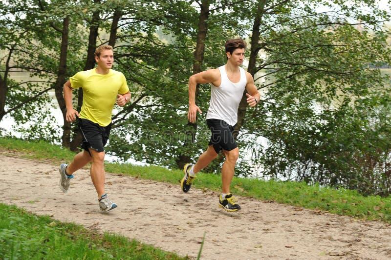 Due atleti degli uomini che passano parco fotografie stock