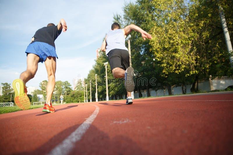 Due atleti maschii che fanno concorrenza sulla pista corrente fotografie stock