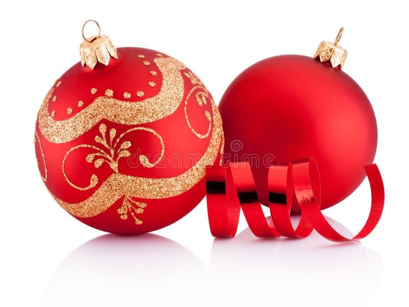Due bagattelle rosse della decorazione di Natale e carta d'arricciatura isolate fotografia stock