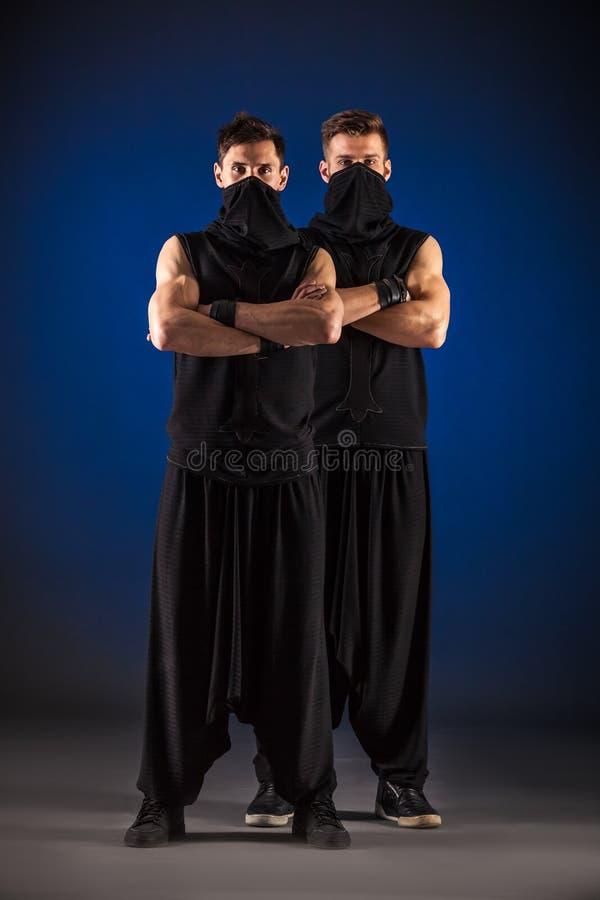Due ballerini maschii che posano in costumi di ninja contro il backgroun blu immagine stock